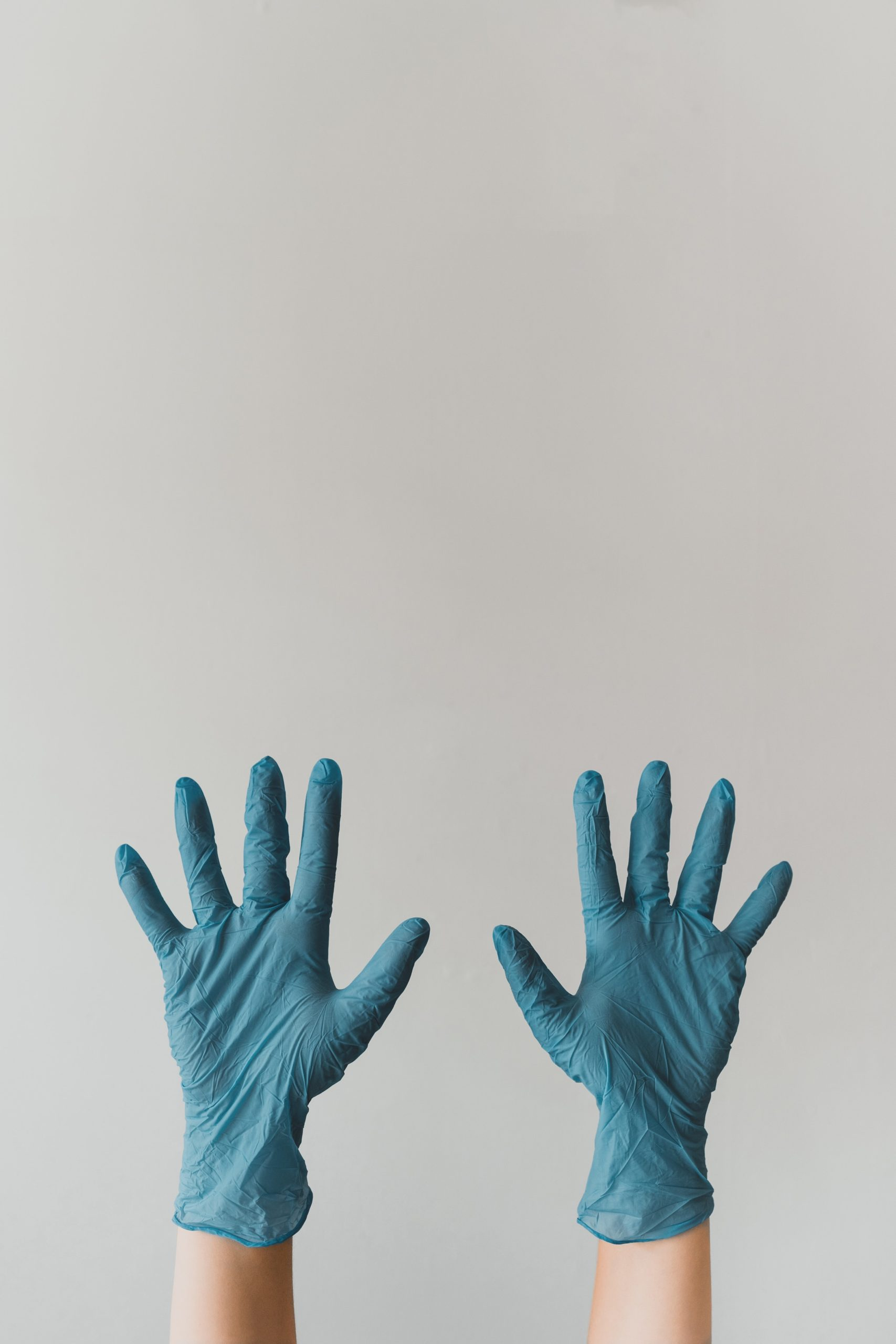 A pair of hands wearing protective gloves. Here are safety protocols you can following to reopen your business during COVID-19.